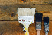 Used paintbrushes on old wooden table — ストック写真