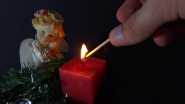 Person igniting a candle with angel figurine — Stock Video