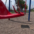 Stock Video: Empty swings swaying at playground