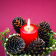 Decorative Christmas Composition From Red Candle, Pine Cones On Red Background — Stock Photo