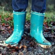 Fall, Autumn concept - Rain boots in mud puddle - Stock Photo