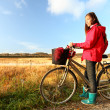 Autumn, fall woman biking on bicycle near field in beautiful landscape. - Stock Photo
