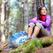 Person hiking - woman hiker sitting in forest - Stock Photo