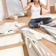 Stock Photo: Wommoving in - furniture assembly frustration