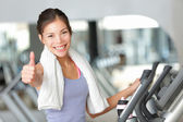 Happy fitness woman thumbs up in gym — Stock Photo