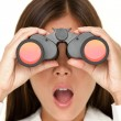 Binoculars woman looking surprised - Stock Photo