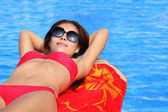 Woman sunbathing by pool — Stock Photo