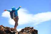 Happy woman hiker reaching her goal at the mountain top summit — Stock Photo