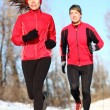 Couple running in winter snow — Stock Photo