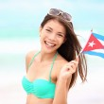 Куба пляж женщина, держащая кубинского флага — Стоковое фото #22919876
