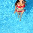 Woman relaxing in swimming pool - Stockfoto