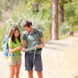 Hikers - hiking couple looking at map — Stock Photo #22923802
