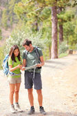 Hikers - hiking couple looking at map — Stock Photo