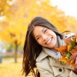 Fall woman playing with leaves — Stockfoto
