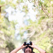 Binoculars - man hiker looking up - Stock Photo