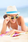 Woman on beach with sunglasses — Stockfoto