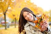 Mujer jugando con hojas de otoño — Foto de Stock