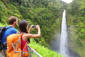 Couple tourists on Hawaii by waterfall — Zdjęcie stockowe
