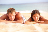 Young couple relaxing sleeping on beach — Photo
