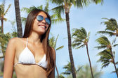Bikini girl wearing sunglasses on palm tree beach — Stock Photo