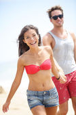 Happy young modern couple on beach — Stock Photo
