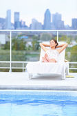 Woman relaxing at city pool — Stock Photo