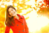 Autumn red trench coat woman in sun flare foliage — Stock Photo