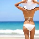 Beach vacation - hot woman in sunhat and bikini — Stock Photo