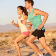 Runners couple running in trail run outside - Stock Photo