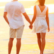Young couple holding hands at beach sunset — Stock Photo