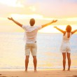 Happy cheering couple enjoying sunset at beach — Stock Photo #25234841