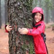 Happy female tree hugger - Stockfoto