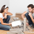 Couple moving in assembling bed furniture — Stock Photo #25235103