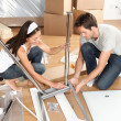 Couple moving in together assembling furniture table — 图库照片