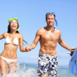 Beach couple fun in water laughing snorkeling — Stock Photo