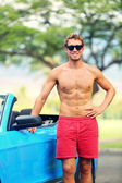 Handsome man with sports car — Stock Photo