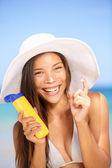 Sunscreen woman applying suntan lotion laughing — Stock Photo