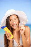 Sunscreen woman applying suntan lotion laughing — Stock Photo