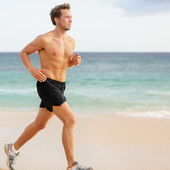 Fitness sports runner man jogging on beach — Stock Photo
