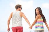Happy cheerful young trendy couple holding hands — Stock Photo