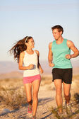 Runners - Active fitness couple running laughing — Stock Photo