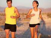 Fitness couple running jogging outside laughing — Stock Photo