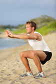 Fitness man training air squat exercise on beach — Stock Photo