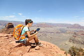 Tablet pc computer vrouw wandelen in de grand canyon — Stockfoto