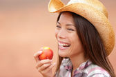 American cowgirl eating peach — Stock Photo
