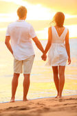 Young couple holding hands at beach sunset — Stok fotoğraf
