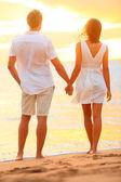 年轻夫妇手牵着手在海滩日落 — 图库照片