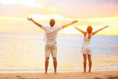 Lycklig jublande par njuter av solnedgången på stranden — Stockfoto