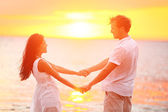 Romantic couple lovers holding hands, beach sunset — Stock Photo