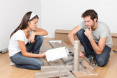 Couple moving in assembling bed furniture — Stock Photo